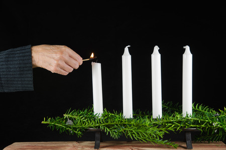 Lighting the first advent candle with a match at a black background 写真素材