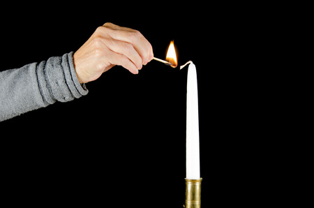 A hand with a match is lighting a white candle photo