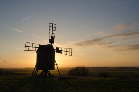 Silhouette of an old wooden windmill on a hill at sunset. From the swedish island Oland, the island of sun and wind photo