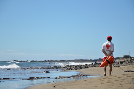 beaches of spain: A red cross lifeguard is patrolling the beach at the resort San Augustin at the island Gran Canaria in Spain