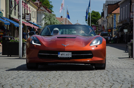 corvette: BORGHOLM SWEDEN  JUNE 13 2015: Chevrolet Corvette parade at the Club Corvette Sweden summer meeting 2015 in the town of Borgholm at the island Oland in Sweden. In front of the parade at this image from the main street in Borgholm is an almost brand new 20