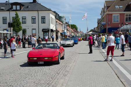 corvette: BORGHOLM SWEDEN  JUNE 13 2015: Chevrolet Corvette parade at the Club Corvette Sweden summer meeting 2015 in the town of Borgholm at the island Oland in Sweden. In front of the parade at this image from the main street in Borgholm is a red 1969 Corvette Ca Editorial