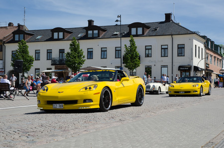 corvette: BORGHOLM SWEDEN  JUNE 13 2015: Chevrolet Corvette parade at the Club Corvette Sweden summer meeting 2015 in the town of Borgholm at the island Oland in Sweden. In front of the parade at this image from the main street in Borgholm is a yellow 2008 Corvette