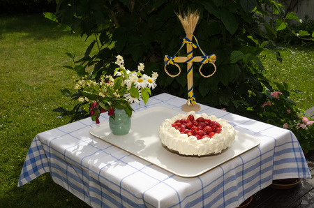 midsummer pole: Homemade strawberry cake on table decorated with flowers and a midsummer pole in a garden