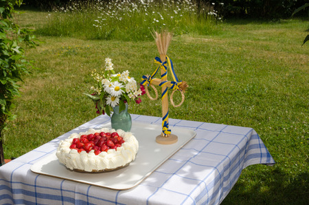 midsummer pole: Table in a garden decorated with a newly made strawberry cake, midsummer pole and flowers Stock Photo
