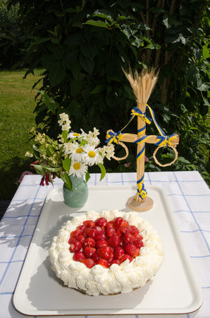 midsummer pole: Fresh strawberry cake at a table with decorations in a garden