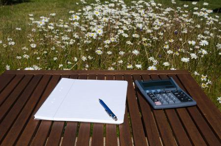 pluma y papel: Trabajar al aire libre lugar con l�piz, papel y calculadora en una mesa en un jard�n con flores