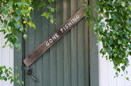 Gone fishing sign at an old green door and green leaves Stock Photo