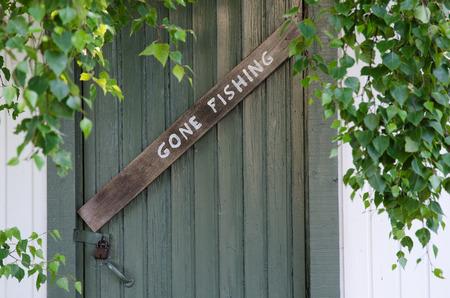 Gone Fishing Zeichen auf einem alten grünen Tür und grünen Blättern