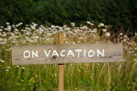 absent: On vacation wooden sign at a pole among white summer flowers Stock Photo