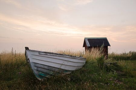 Oude verlaten roeiboot op de grond onder het gras aan de kust van de Oostzee in Zweden Stockfoto