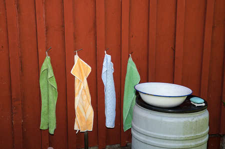 the place is outdoor: An outdoor wash place with colorful towels