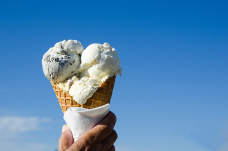 blue sky: Hand is holding an ice cream cone at a blue sky