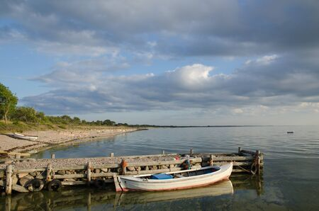 oland: Sunlit old wooden boat at an old- fashioned pier in the Baltic Sea at the island Oland in Sweden