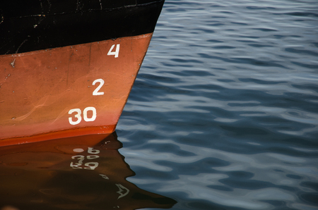 depth measurement: Numbers and reflections of a bow of a ship in water Stock Photo