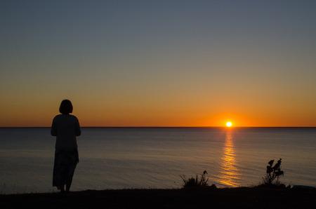 mujer mirando el horizonte: Mujer viendo la puesta de sol en el horizonte de la costa Foto de archivo