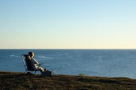 mujer mirando el horizonte: Mujer sentada en una silla con una cesta en la playa mirando el mar azul