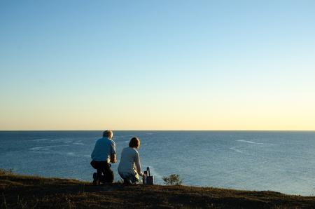 mujer mirando el horizonte: Matrimonios de edad por la playa en el último sol de la tarde