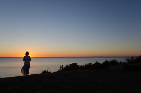 mujer mirando el horizonte: Mujer que mira la puesta de sol en el horizonte de la costa