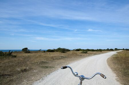 dirt road recreation: Biking on a gravel road along the coast at the swedish island Oland in the Baltic Sea