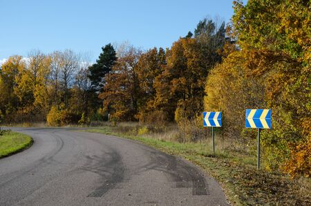 roadsigns: Roadsigns with arrows at roadside in a colorful landscape at fall Stock Photo