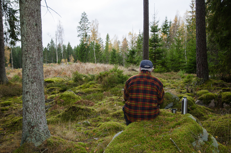 sweden resting: Senior lumberjack sitting on a mossy rock in a green forest Stock Photo