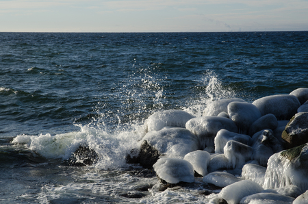 ice covered: Splashing waves at ice covered rocks by a coast with a deep blue water Stock Photo