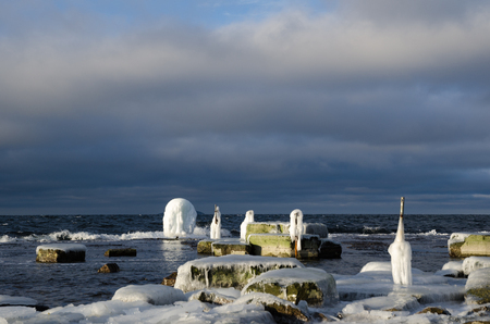 ice covered: Ice covered fence posts by a rocky coast at the swedish island Oland in the Baltic Sea
