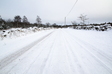 low perspective: Low perspective image of a winter landscape with a snowy road surrounded of stone walls