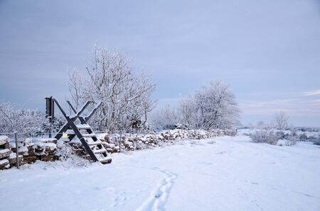 stile: Winter landscape with a stile at a snow covered stone wall