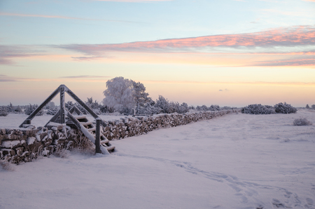 Dawn at a winter landscape with a stile by stone wall Standard-Bild