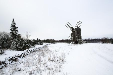 wintery day: Old wooden windmill by roadside in a snowy swedish landscape Stock Photo