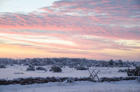 stile: Stile at a stone wall by sunrise in a winter landscape Stock Photo