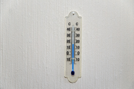 celcius: Single indoors celcius thermometer at a bright wall