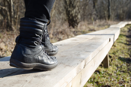 activ: Closeup of a boots walking on a wooden footpath
