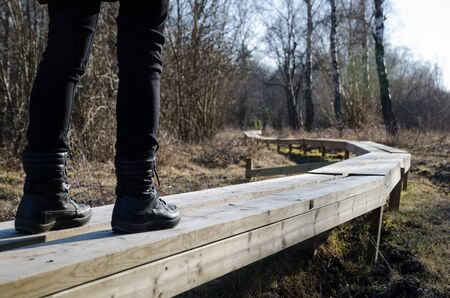 newly: Legs with boots walks at a newly made wooden footpath in the nature Stock Photo
