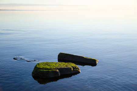 absolutely: Green limestone rocks in an absolutely calm water