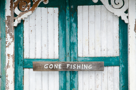 Closeup of a gone fishing sign on a weathered door with cracked painting in white and green Stock Photo