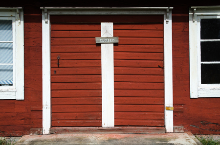 not open: Old red exterior wooden doors with a wooden closed sign
