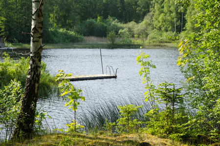 a bathing place: View at a wooden bath pier by a lake in a green and sunny landscape