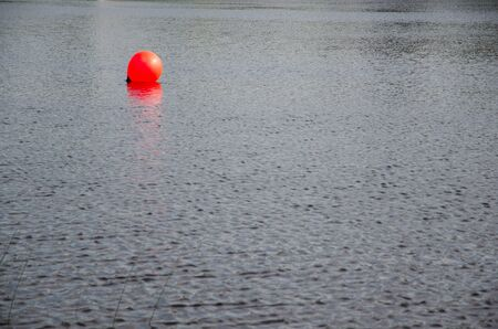 circular water ripple: Single shiny red buoy in blue rippled water Stock Photo
