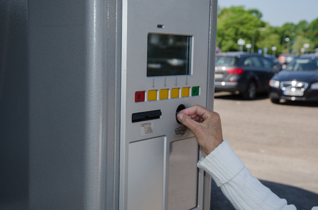 parking facilities: Paying fee in a parking automate with blurred cars in the background
