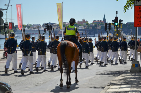 escorting: Stockholm, Sweden - June 13, 2016: Police escort when the royal guards marches for changing the guards at the royal castle in Stockholm, Sweden