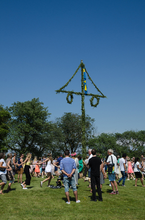 midsummer pole: Borgholm, Oland, Sweden - June 24, 2016: People celebrates midsummer by dancing around a maypole