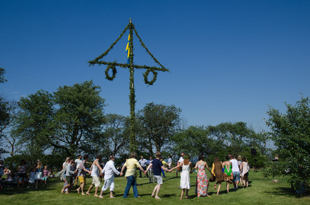 midsummer pole: Borgholm, Oland, Sweden - June 24, 2016: Dancing around the maypole when the swedes celebrates midsummer