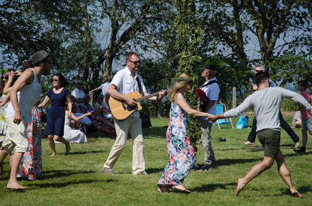 Borgholm, Oland, Sweden - June 24, 2016: Musicians and people dancing around a midsummer pole to celebrate midsummer in Sweden