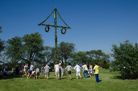 midsummer pole: Borgholm, Oland, Sweden - June 24, 2016: Swedes celebrating midsummer by dancing around a midsummer pole