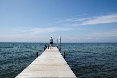 mujer mirando el horizonte: Mujer mirando el horizonte en un viejo muelle de madera del baño Foto de archivo