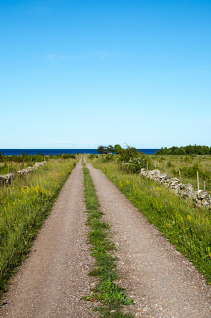 Gravel road at the swedish island Oland straight to the coast of the Baltic Sea Stock Photo