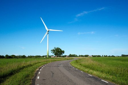road side: Windmill by a country road side in a green landscape Stock Photo